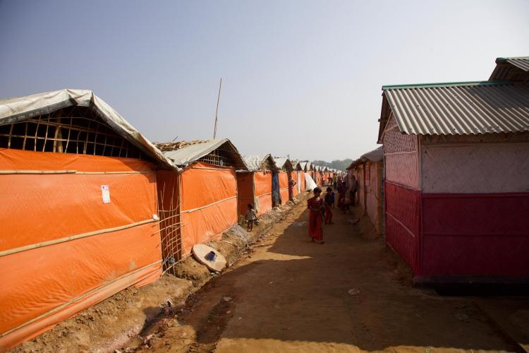 Rows of makeshift housing with plastic sidewalls and metal roofs