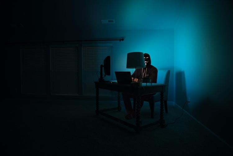 Hacker wearing a mask in dark room sitting at a computer