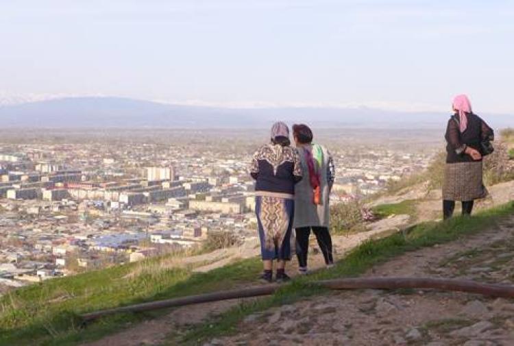3 women standing on hill overlook a village