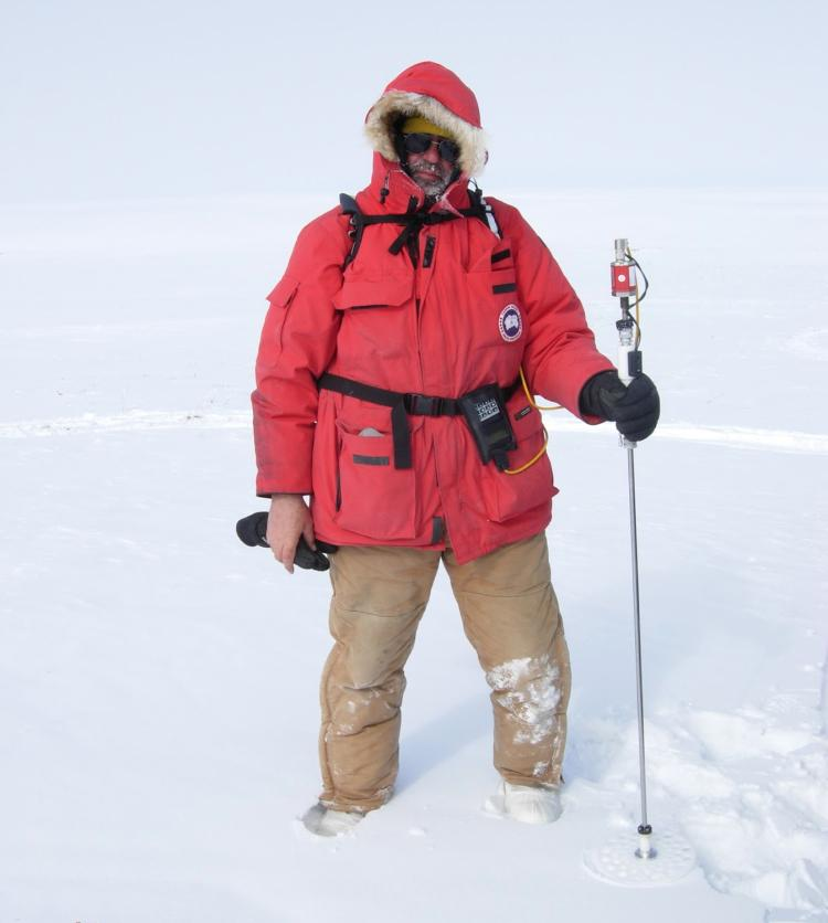 Man in red parka standing in snow