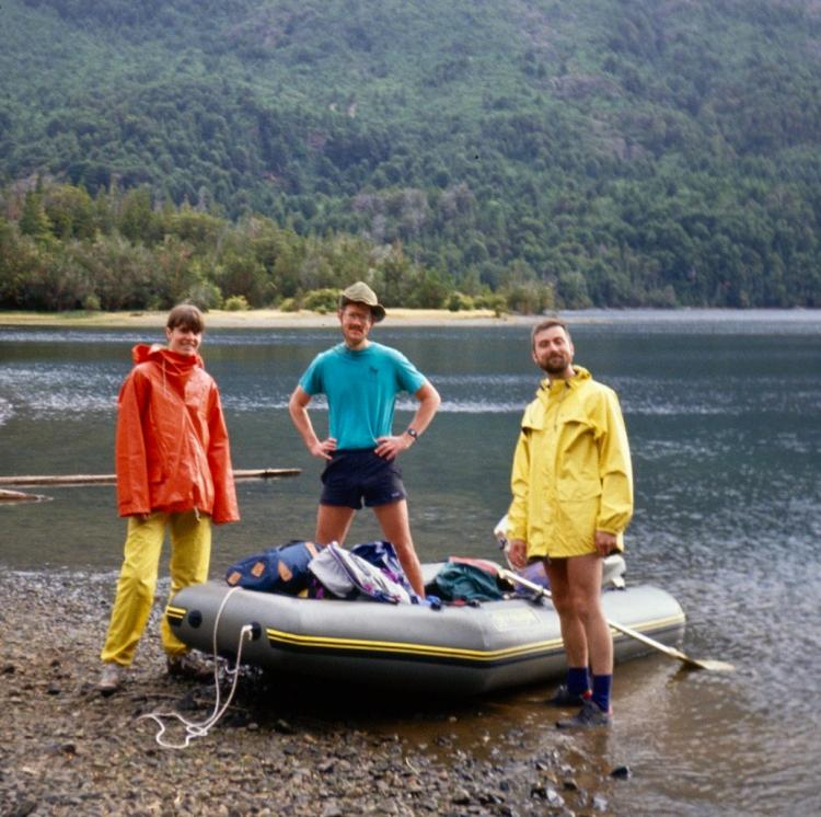 3 men posing in and near inflatable raft on a lake beach