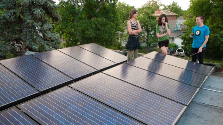 3 people standing next to series of solar panels