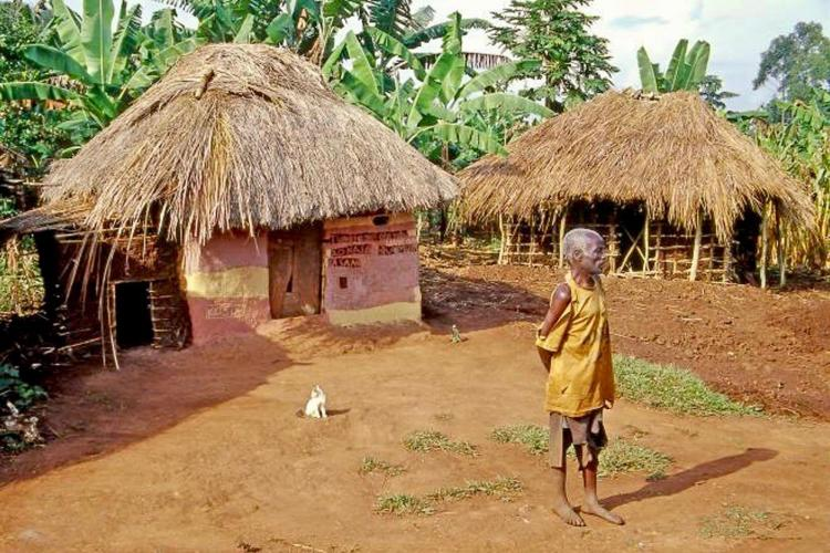 old man standing in front of thatched roof hut