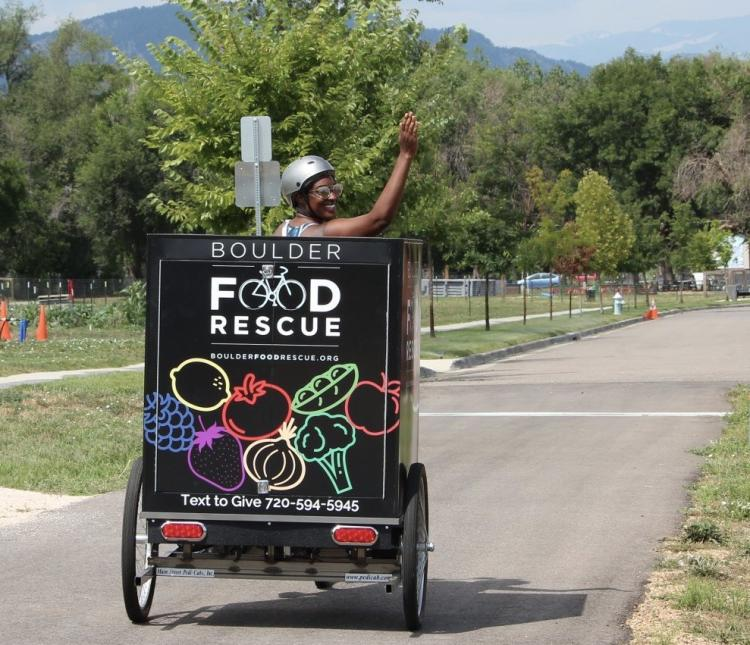 man pedaling a Boulder Food Rescure cart