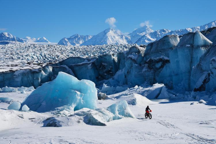 Persion riding bicycle on Arctic snow
