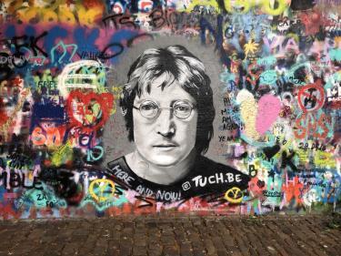 Wall of graffiti with illustration of John Lennon