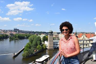 Student posing overlooking landscape of river and the city of Prague