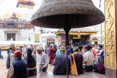 Crowd in Nepal city with engraved metal bell in foreground
