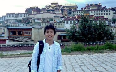 Student posing with Tibetan city in background