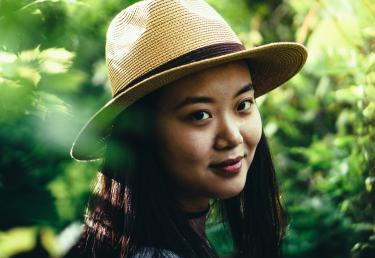 Young woman smiling and wearing straw fedora