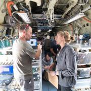 Emily Fischer and crew standing in fuselage of research plane