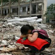 Woman squatting, burying head in arms, in front of earthquake devastation of Sichuan China