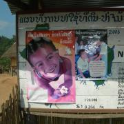 Public postings on a board with various posters and info in a foreign language