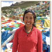 Emily Yeh in foreground with Tibetan landscape and prayer flags on the ground behind her.