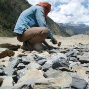 Person chipping rocks with a hammer in a mountain landscape