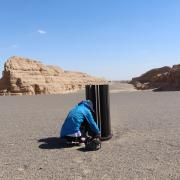 Woman squatting by research equipment in rocky desert-like landscape
