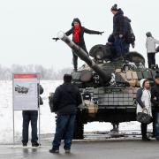 Non-military people climbing on tanks, posing for photos.