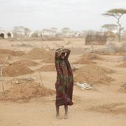 African woman standing in drought-affected area