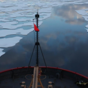 Bow of ship sailing over melting arctic ice