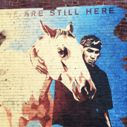 Grafitti on brick wall of native american with a horse