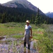 Woman standing in mountain puddle with drill and mountain backdrop