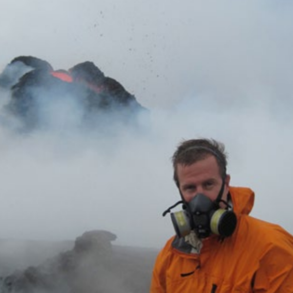 A researcher wearing a gas mask and looking at a volcano