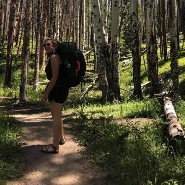 Women hiking in an aspen forest.