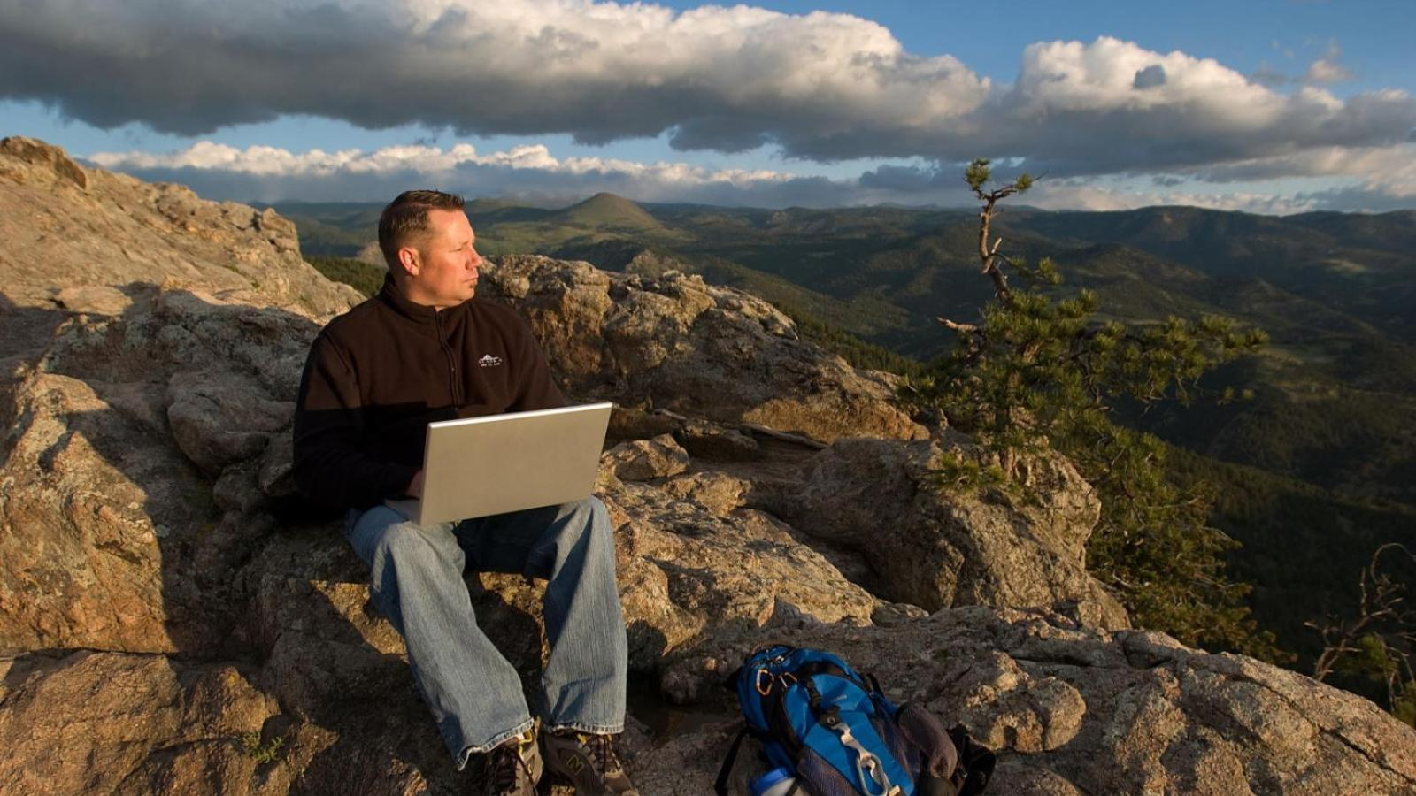 Man with laptop on a rocky overlook in the mountains