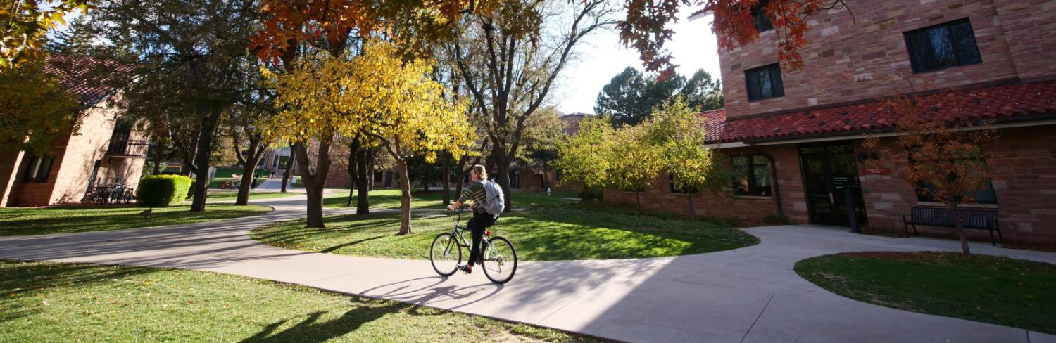 Student riding her bike through campus in the fall
