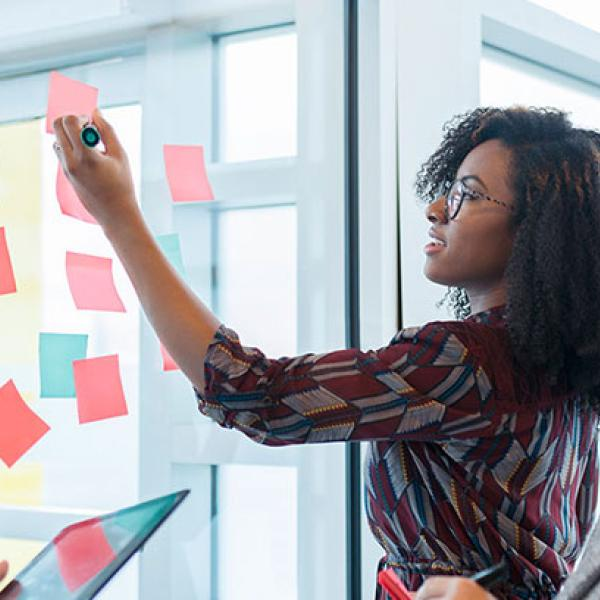 People brainstorming with post-it notes on a wall
