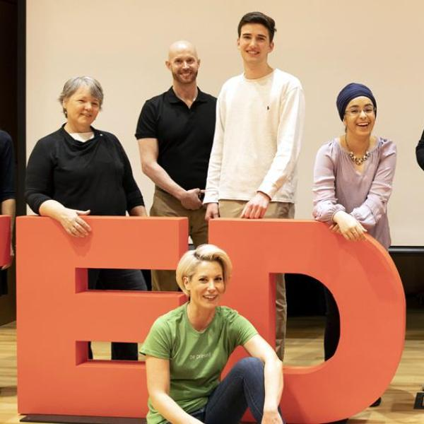 Students in front of a TEDxCU sign