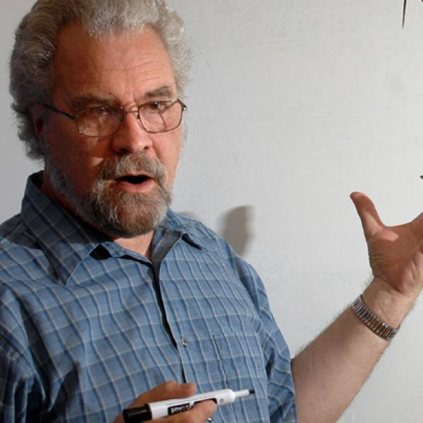 Linguistics professor in front of a white board