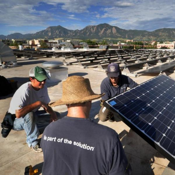 People on a roof working with solar panels