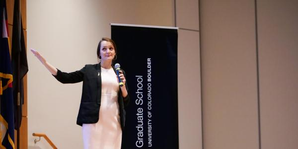 Jocelyn gestures on stage at the 3MT competition