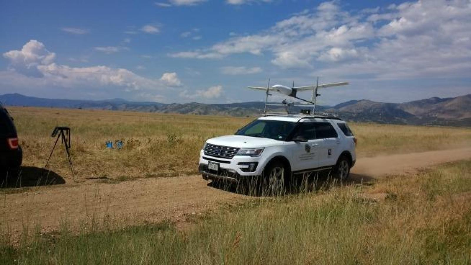 The SuperSwift fixed-wing drone, which is being used this summer in soil moisture mapping work being done in Yuma, as it is roof-launched for validation testing from the top of a University of Colorado vehicle.