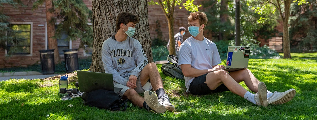 two students sitting outside on laptops