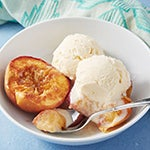 Baked peaches in a bowl with vanilla ice cream.
