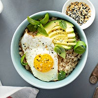 Bowl of oatmeal topped with cheese, veggies and an egg