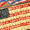 A fruit pizza with bananas and berries in an American flag arrangement
