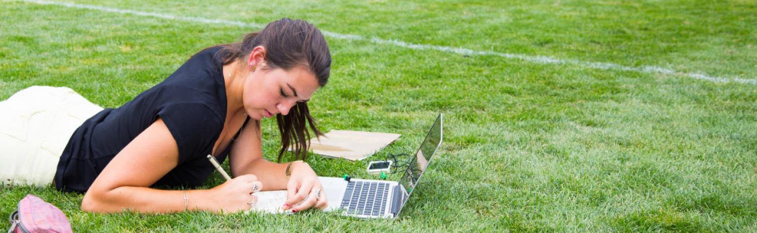 Student taking notes in front of her laptop while lying down at Farrand Field.