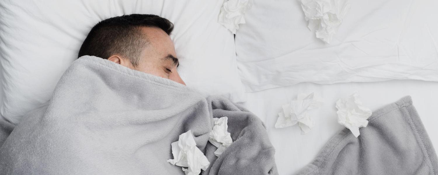 Man in bed with tissues