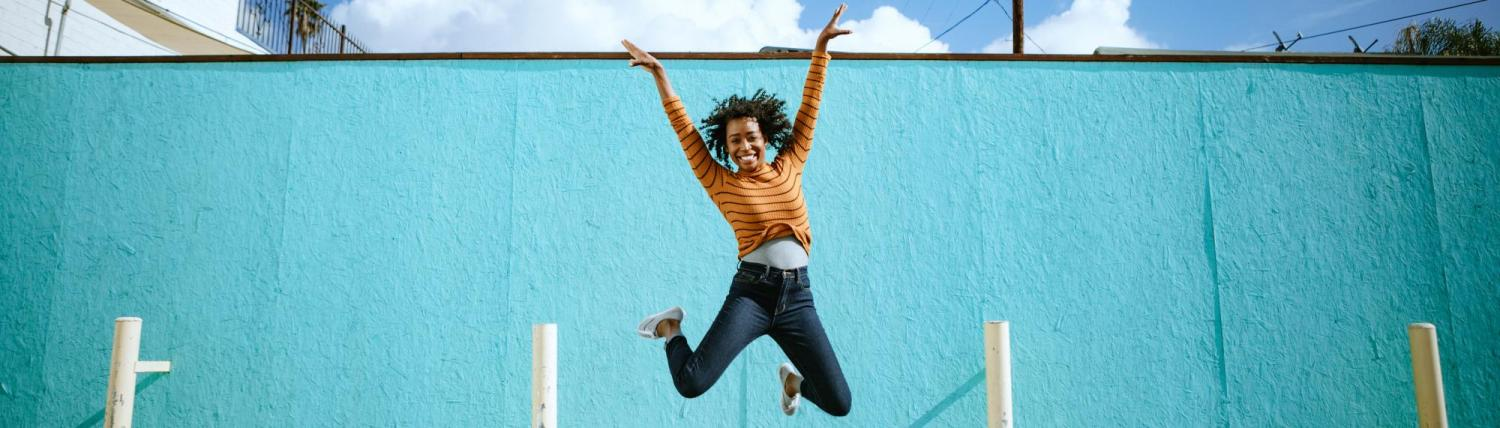 Woman jumping up in celebration outside