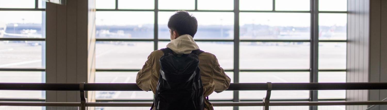 Man standing in front of bay windows at the airport