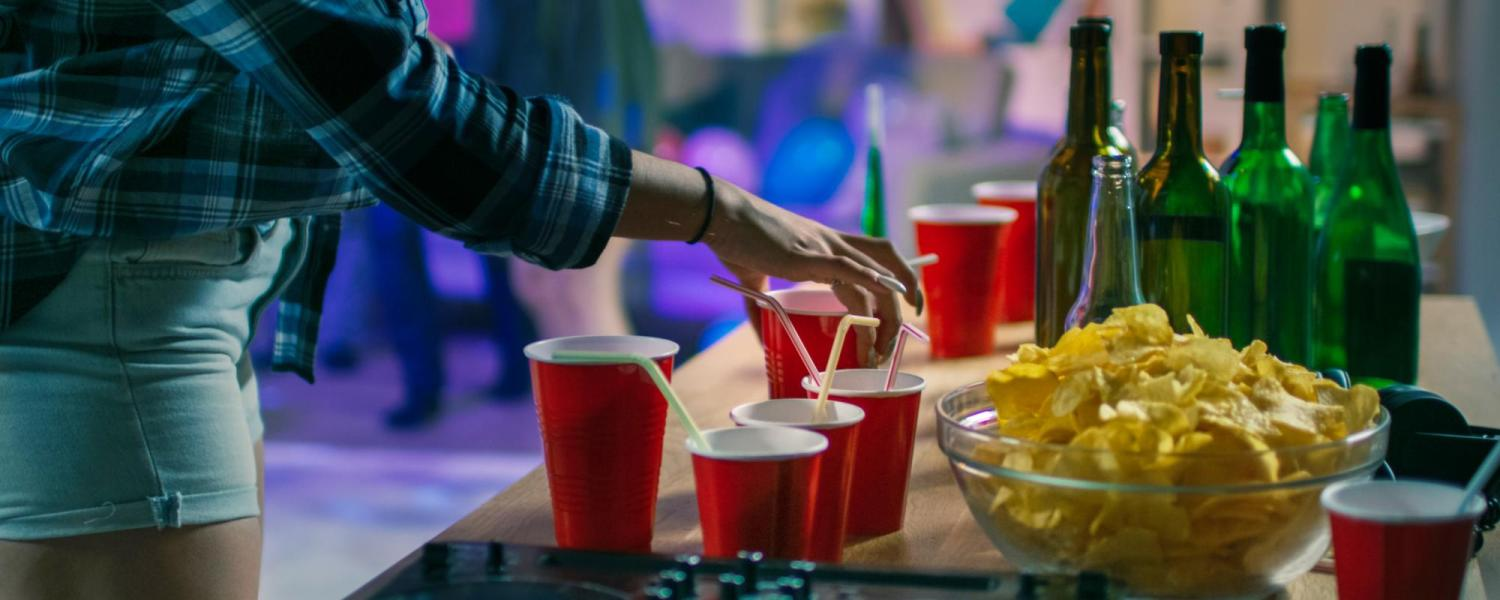 Girl grabbing a solo cup off a table at a party