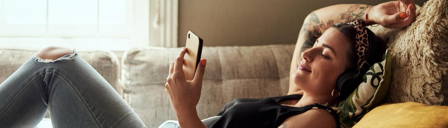 Girl laying on couch wearing headphones in a relaxed position looking at her phone.