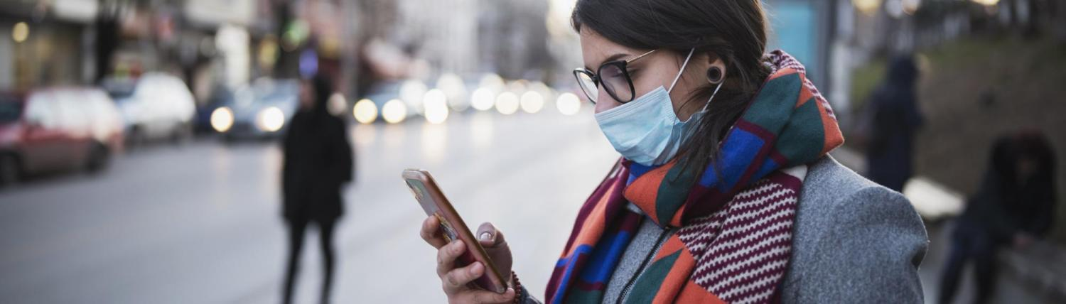 Woman wearing a mask looking at her phone on an empty street.