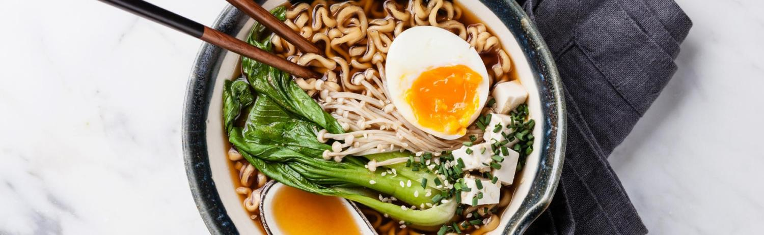 Bowl of ramen noodles in broth with eggs, seaweed and bok choy