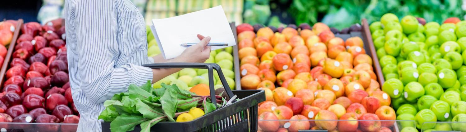 Woman holding a list and grocery basket while standing in front of a produce bin.