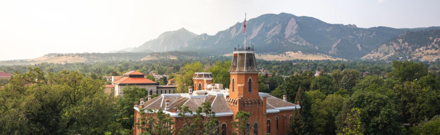 Aerial view of old main on a misty morning in spring with the flatirons in the background.