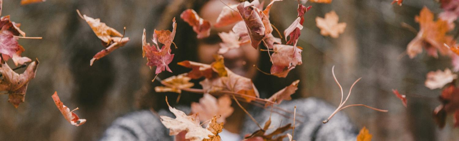 Girl throwing colorful fall leaves in the air in front of her face.